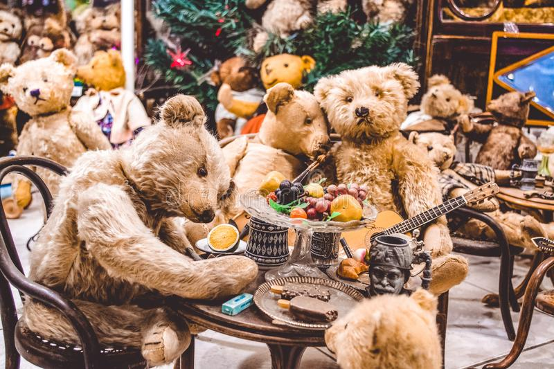 Los osos marrones del peluche tienen un buen rato y comen el helado, tocan la guitarra Exposición de juguetes Partido en Años Nue imágenes de archivo libres de regalías