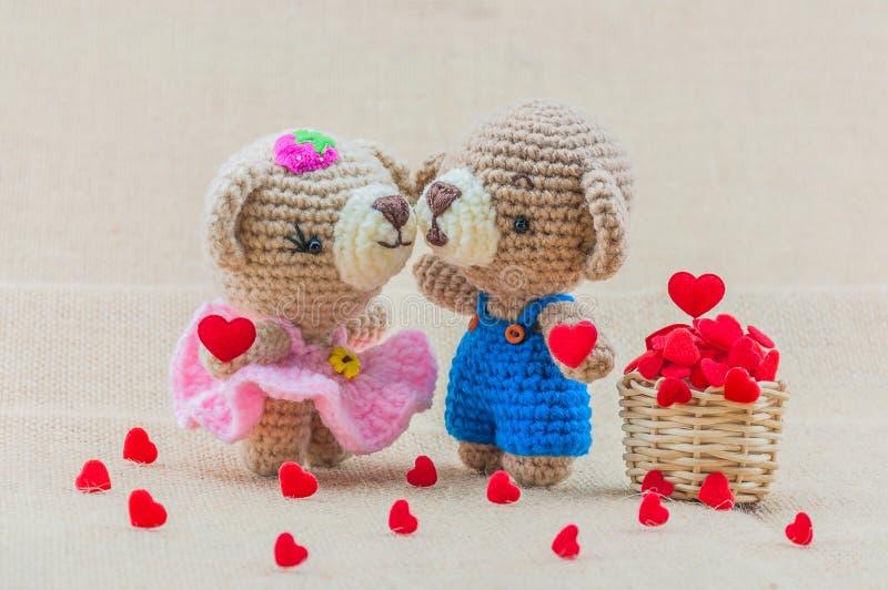 Los osos preciosos del bebé que se besan hacen a ganchillo la muñeca con la cesta de los corazones fotos de archivo libres de regalías