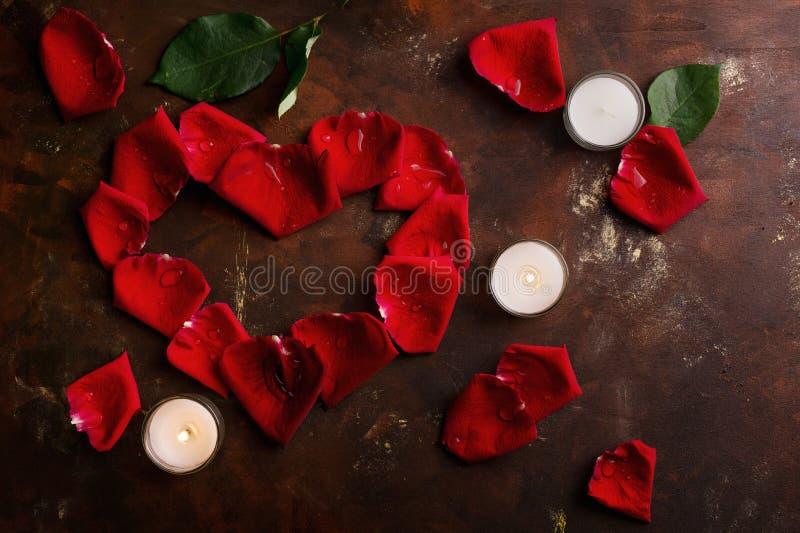 Los pétalos color de rosa rojos en corazón forman con las velas blancas en marrón oscuro y fondo de oro Amor, romance, aniversari foto de archivo