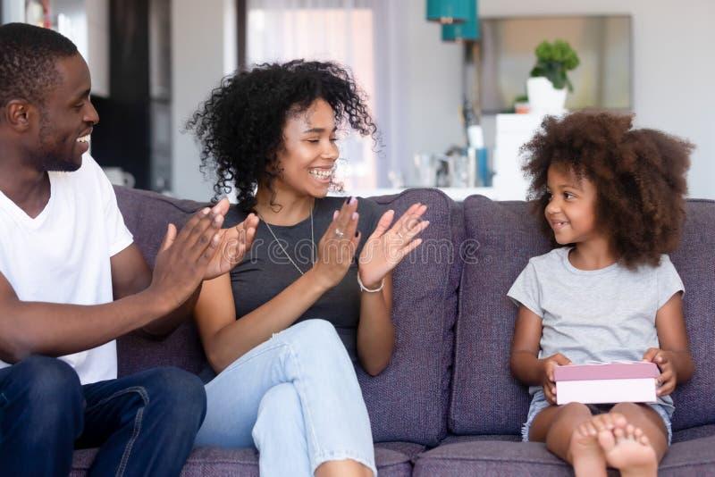 Los padres africanos de amor aplauden las manos que felicitan poco feliz cumpleaños de la hija foto de archivo libre de regalías