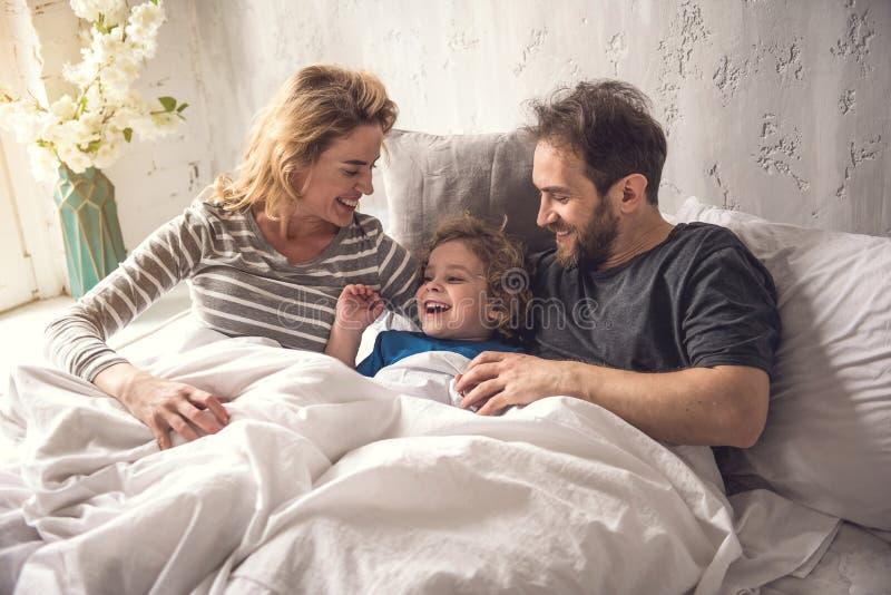 Los padres alegres están abrazando al hijo mientras que permanecen en ropa de cama imagenes de archivo