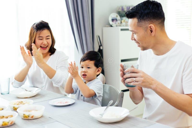 Los padres asiáticos que aplauden las manos y que dan el cumplido como su niño hacen buen trabajo mientras que teniendo comida ju imagen de archivo