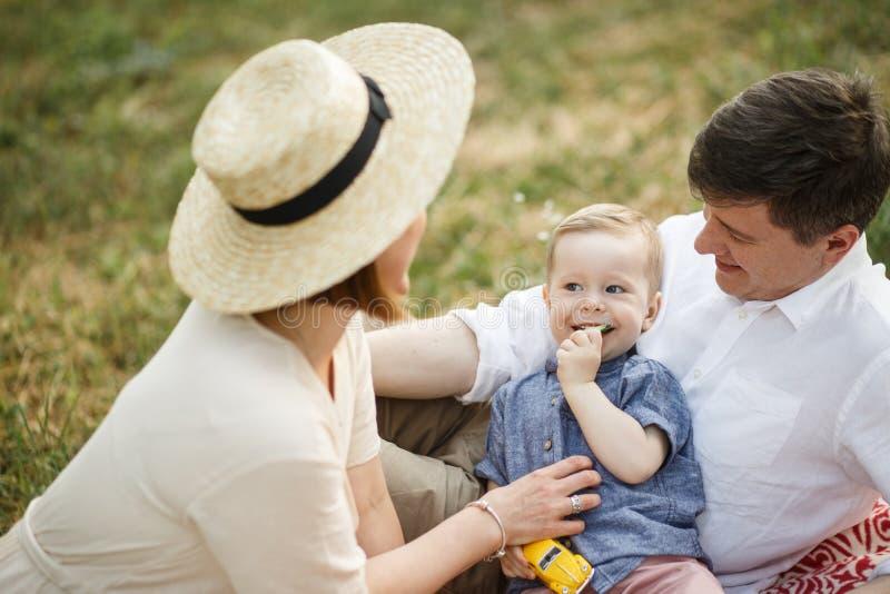 Los padres con el niño se sientan en el parque Lo miran El niño come el pepino fotos de archivo