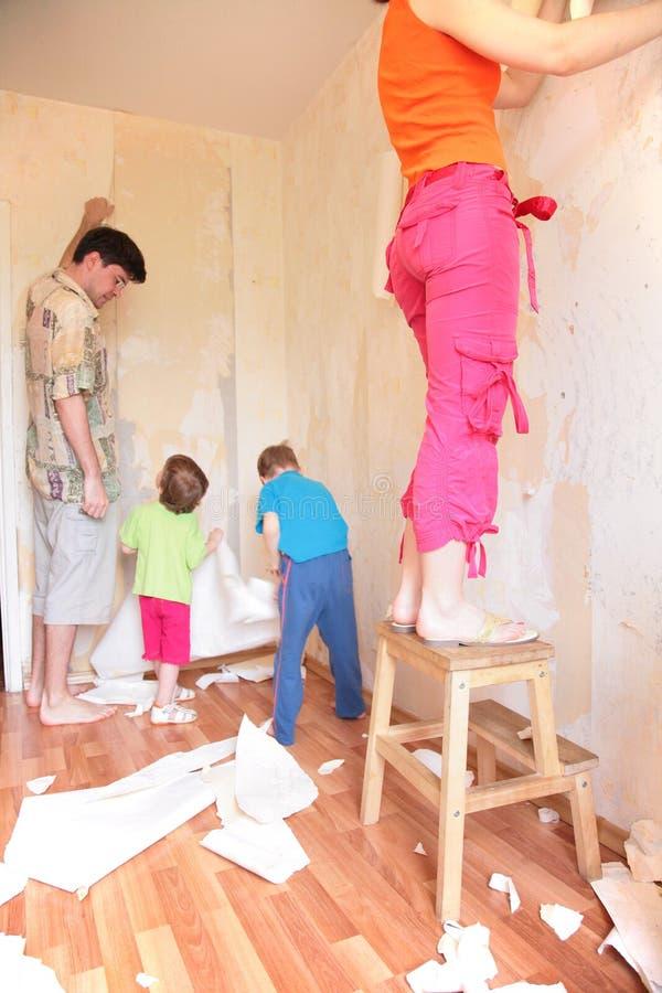 Los padres con los niños rompen los papeles pintados de la pared fotografía de archivo libre de regalías