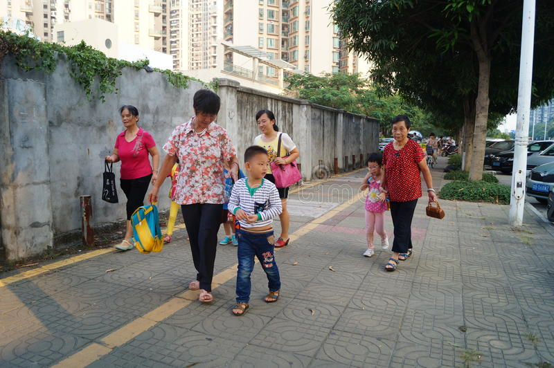 Los padres de la guardería escogen para arriba a los niños van a casa después de escuela, imagen de archivo