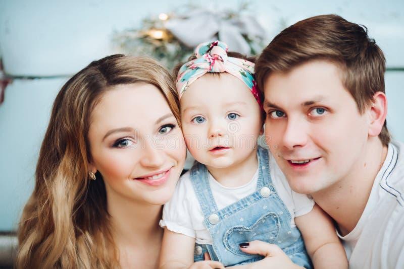 Los padres de moda que se sostienen encendido dan la pequeña hija linda, colocándose cerca del coche retro azul imagenes de archivo