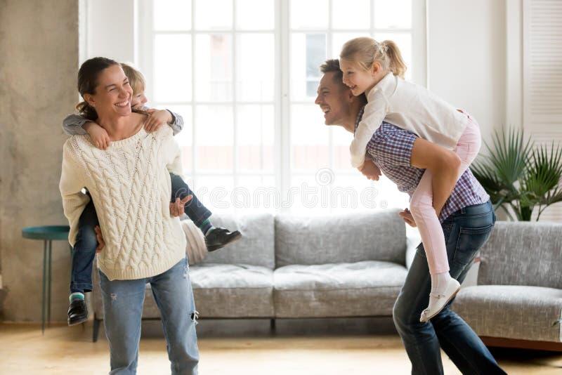 Los padres de risa que dan a niños llevan a cuestas el paseo que juega juntos fotografía de archivo libre de regalías