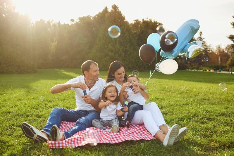 Los padres desean a niños al feliz cumpleaños en el parque fotografía de archivo
