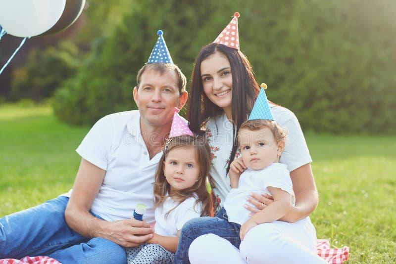 Los padres desean a niños al feliz cumpleaños en el parque foto de archivo