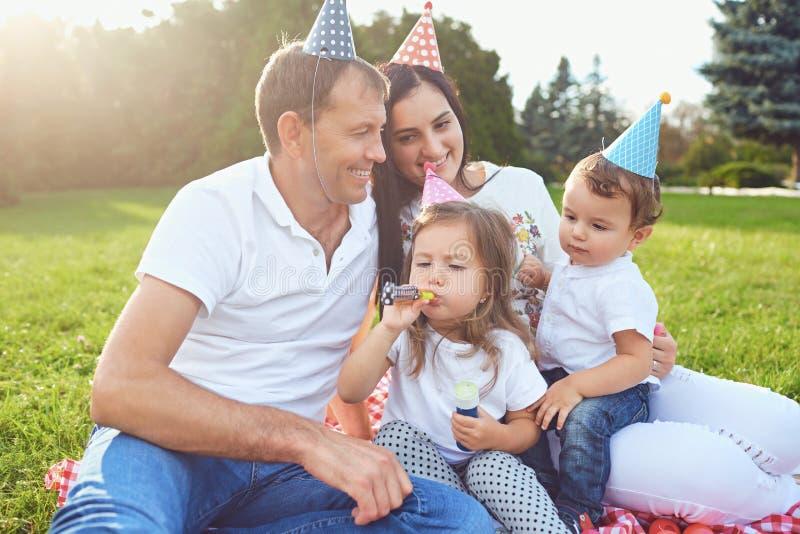 Los padres desean a niños al feliz cumpleaños en el parque imagen de archivo libre de regalías