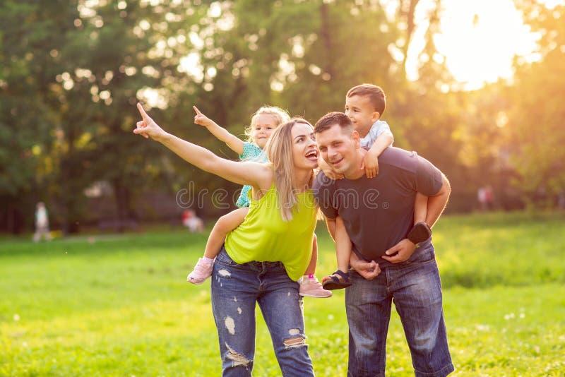 Los padres divertidos que dan a niños llevan a cuestas paseo en parque fotos de archivo libres de regalías