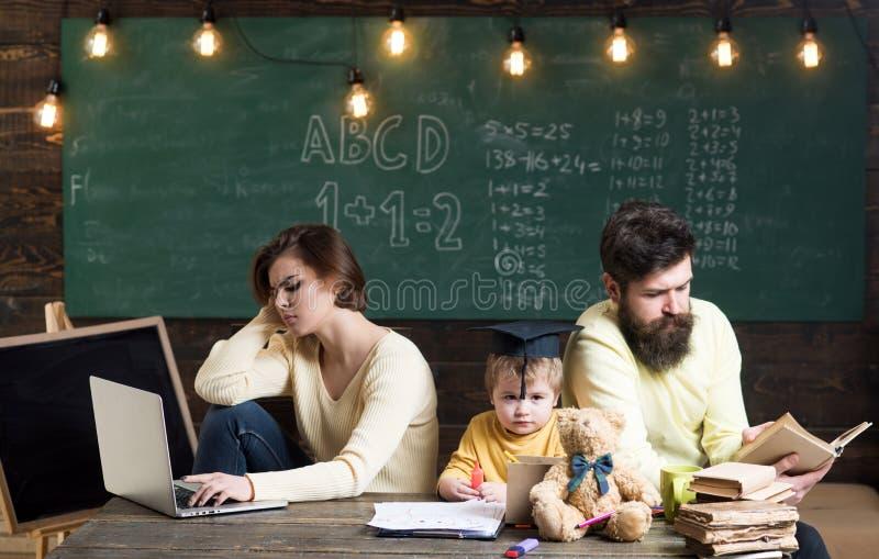 Los padres en caras ocupadas no cuidan sobre la educación de su hijo Concepto ocupado de los padres Libro de lectura del padre, t fotos de archivo libres de regalías