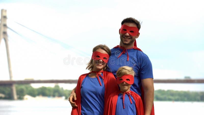 Los padres en super héroe visten el juego con el hijo, psicoterapia para hacer frente a problemas fotografía de archivo libre de regalías