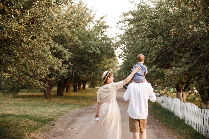 Los padres están caminando abajo del camino en jardín El individuo está cuidando a su hijo en sus hombros fotografía de archivo libre de regalías