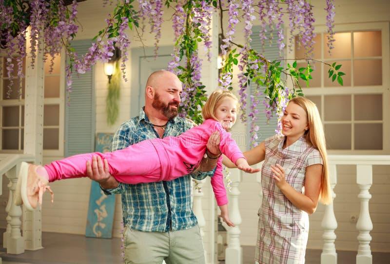 Los padres felices con la hija se divierten que juega deteniendo al niño en sus manos, en domicilio familiar del verano del patio imagen de archivo libre de regalías