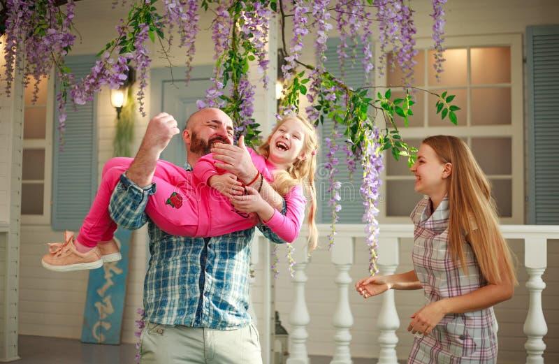 Los padres felices con la hija se divierten que juega deteniendo al niño en sus manos, en domicilio familiar del verano del patio fotografía de archivo