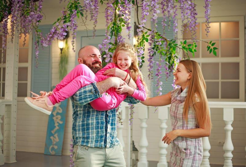 Los padres felices con la hija se divierten que juega deteniendo al niño en sus manos, en domicilio familiar del verano del patio foto de archivo