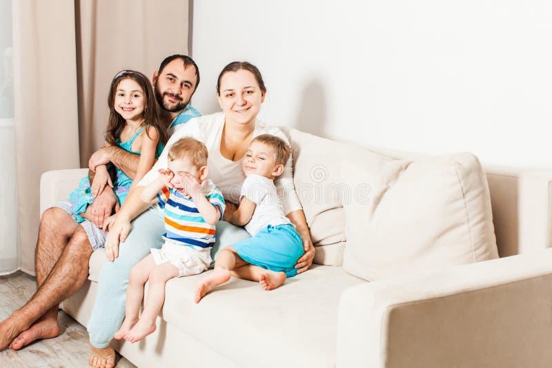 Los padres felices con los niños se están sentando en el sofá imagenes de archivo