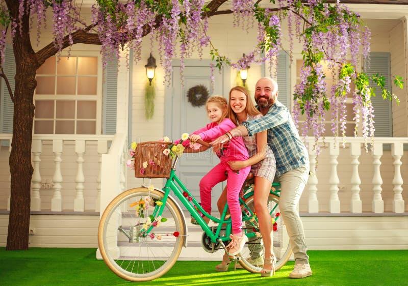 Los padres felices con un niño, hija, aprenden montar una bici, vacaciones de verano de la forma de vida de la familia en casa imagen de archivo libre de regalías