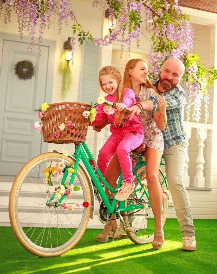 Los padres felices con un niño, hija, aprenden montar una bici, vacaciones de verano de la forma de vida de la familia en casa imagen de archivo