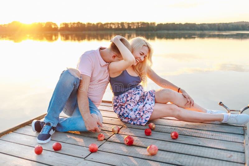 Los padres futuros se divierten en la orilla del lago foto de archivo