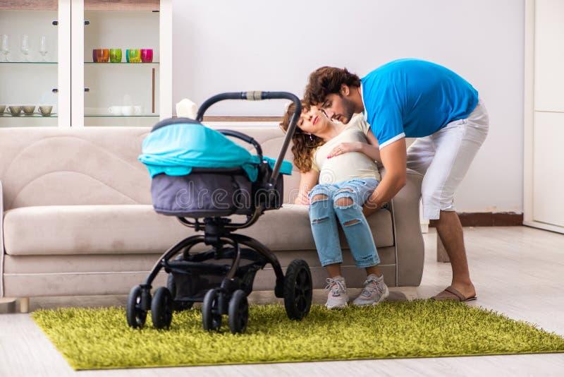 Los padres jovenes con el bebé que cuenta con nueva llegada foto de archivo libre de regalías