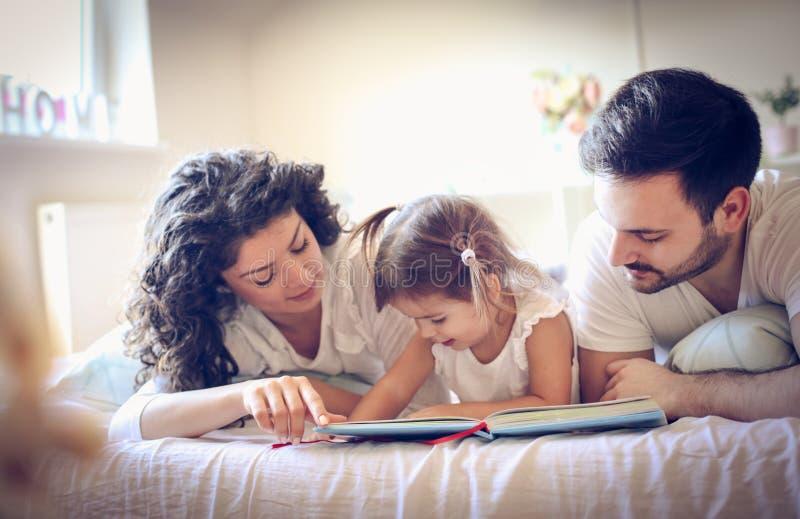 Los padres jovenes con su niña que mira color reservan Mañana fotografía de archivo libre de regalías