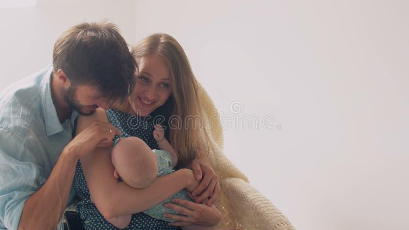 Los padres jovenes felices hermosos sonríen a su madre recién nacida preciosa del hijo que calma a su bebé en una mecedora 4K foto de archivo