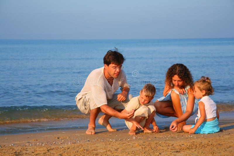 Los padres juegan con los niños que encuentran shelles foto de archivo