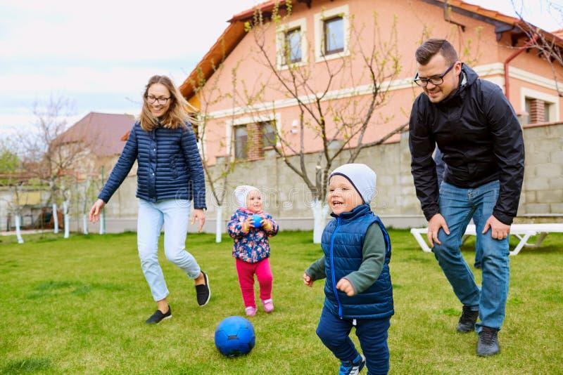 Los padres, la madre, el padre y el hijo juegan en la yarda de la casa en GR fotografía de archivo