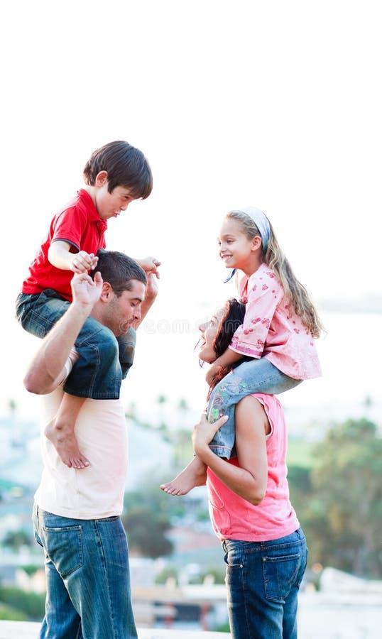 Los padres que dan a sus niños llevan a cuestas paseos imagenes de archivo