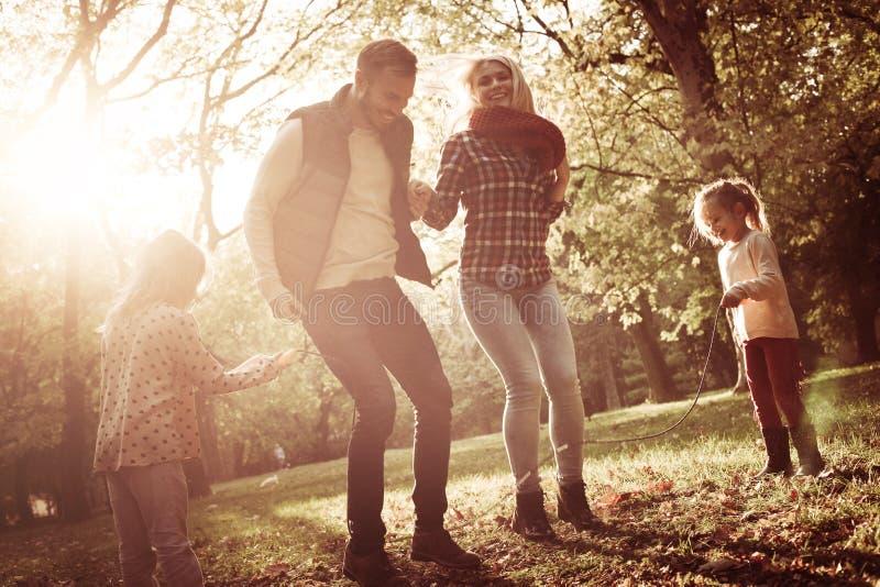 Los padres que saltan a través de comba y de su holdi de las hijas fotografía de archivo