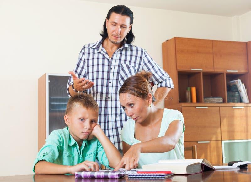 Los padres regañan a su hijo del alumno con bajo nivel de rendimiento imágenes de archivo libres de regalías