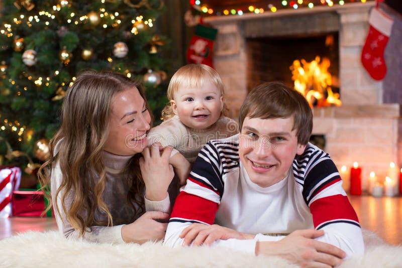Los padres y el muchacho felices del niño se divierten cerca del árbol de navidad en casa Padre, madre, hijo que celebra Año Nuev foto de archivo