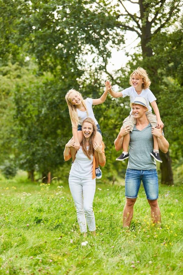 Los padres y los niños gozan el llevar a cuestas fotografía de archivo libre de regalías