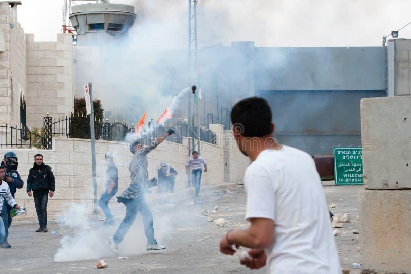 Los palestinos lanzan detrás el gas lacrimógeno imágenes de archivo libres de regalías