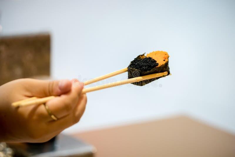 Los palillos ascendentes cercanos se sostienen en la comida japonesa del camarón del huevo del sushi para sano sushi del unagi, m fotografía de archivo libre de regalías