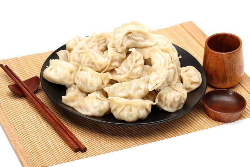 Los palillos cogen las bolas de masa hervida de Boilded Chineses de una placa La bola de masa hervida, llamada Jiaozi en chino, e imagenes de archivo