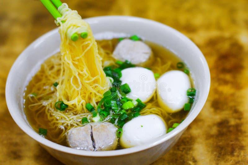 Los palillos cogen los tallarines de la bola de pescados de Hong Kong con cebolletas en el top imágenes de archivo libres de regalías