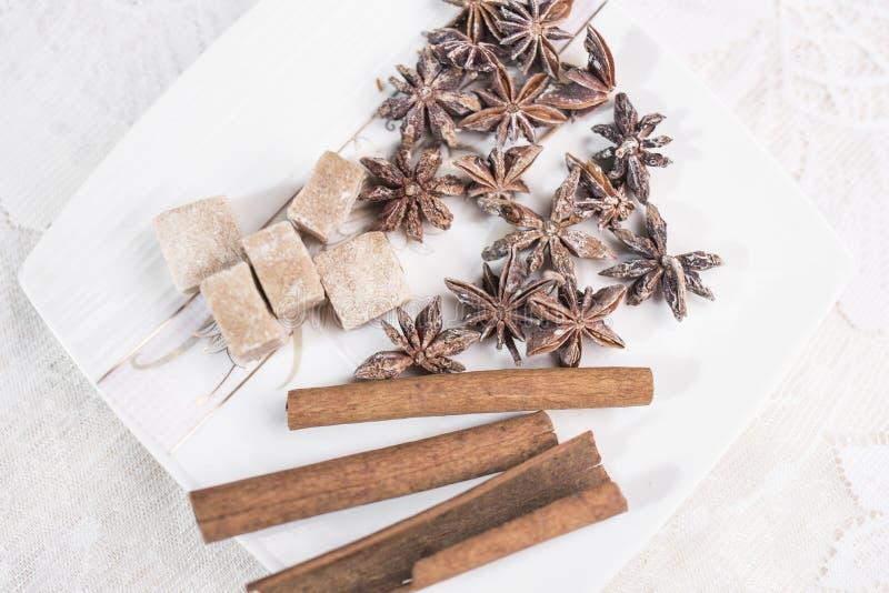 Los palillos de canela, anís protagonizan y juntan las piezas de mentira del azúcar marrón en un platillo blanco de la verruga imagenes de archivo