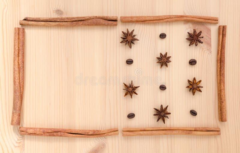 Los palillos de canela, el anís de estrella y los granos de café pusieron en b de madera fotos de archivo libres de regalías
