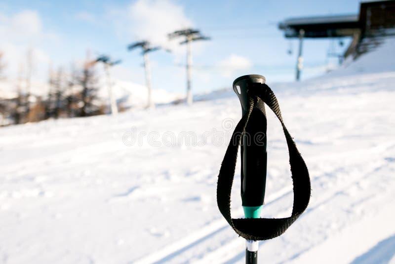 Los palillos del esquí se cierran para arriba con el fondo de la montaña imagen de archivo libre de regalías