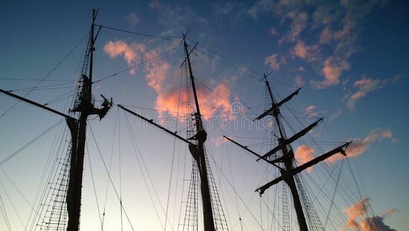Los palos oscuros altos, hermosos de una nave vieja en el fondo de la púrpura colorearon el cielo de la puesta del sol Viaje romá imagen de archivo
