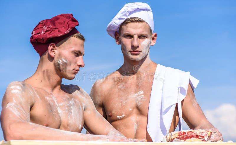 Los panaderos en sombreros con aspecto atractivo trabajan juntos, amasando la pasta La brigada de amigos musculares trabaja en el imagen de archivo libre de regalías