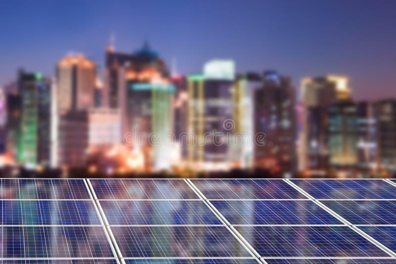Los paneles azules de la célula solar, horizonte borroso de la ciudad iluminado en la noche foto de archivo