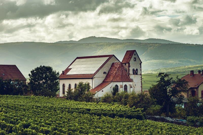 Los paneles fotovoltaicos en el tejado de la iglesia en Alsacia foto de archivo libre de regalías