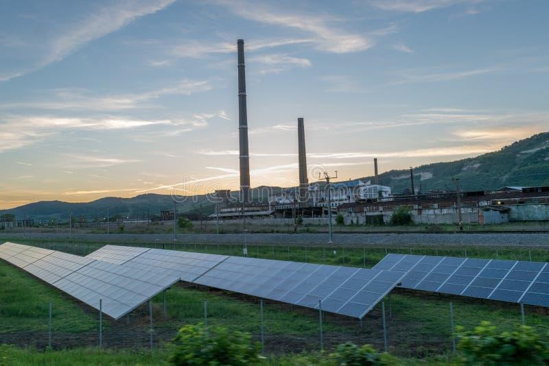 Los paneles solares cerca de una central eléctrica con los tubos fotos de archivo libres de regalías