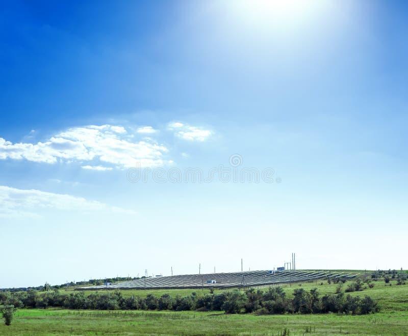 Los paneles solares colocan en paisaje del verano y cielo azul con las nubes y el sol foto de archivo