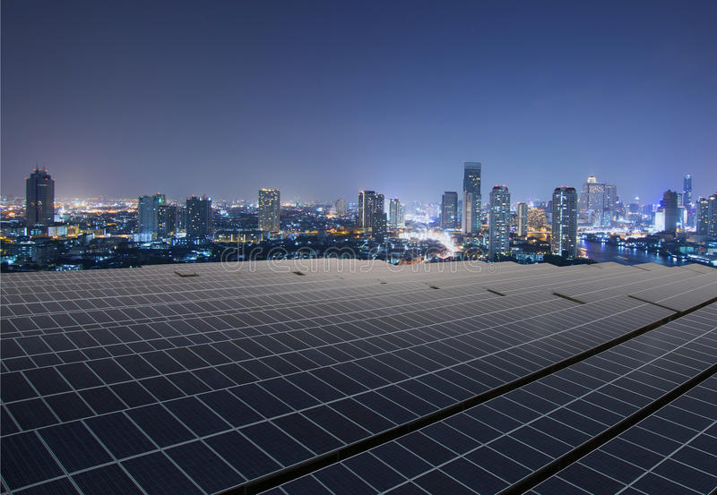 Los paneles solares con la ciudad crepuscular imagenes de archivo