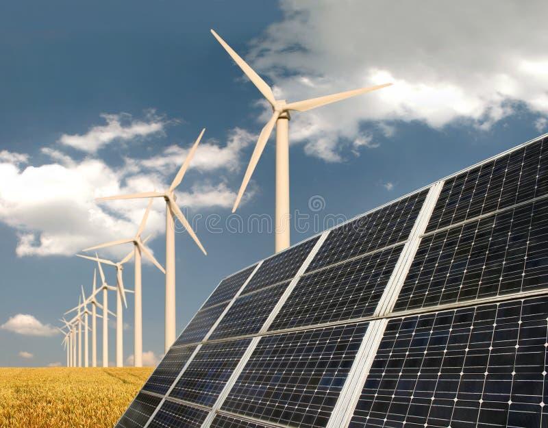 Los paneles solares delante de las centrales de energía eólica imagenes de archivo